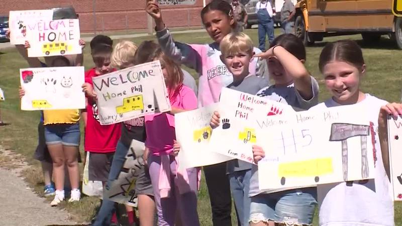 Students lined the streets to welcome their bus driver home.